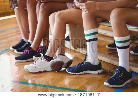 High school kids sitting on the bench in basketball court