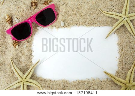 Pink sun glasses and starfishes on sand beach frame with copy space