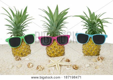 Picture of three pineapple on the sand with sun glasses starfish and seashells. Isolated on white background