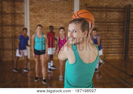 Portrait of high school kids playing basketball in the court