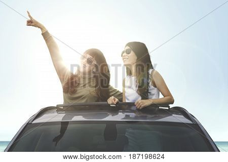 Two young female wearing sun glasses looking something on a car sunroof on the beach
