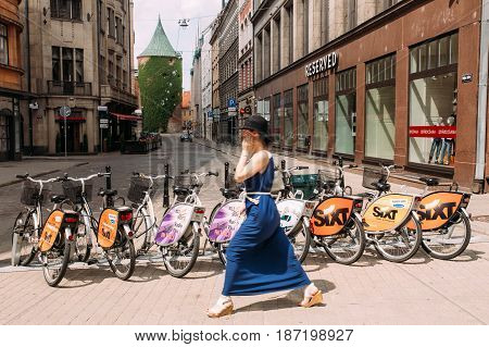 Riga, Latvia - July 2, 2016: Woman Walking Near Row Of Colorful Bicycles For Rent At Municipal Bike Parking In Kalku Street, Popular Showplace Of Old Town In Summer Day.