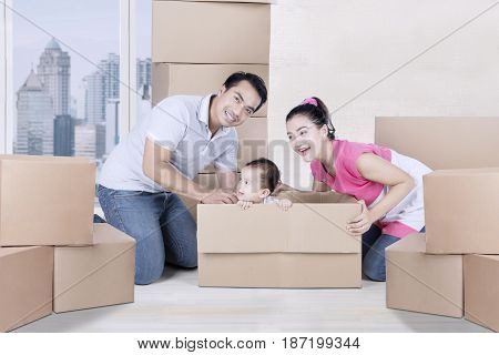 Picture of young family playing with cardboard boxes while sitting in the new apartment
