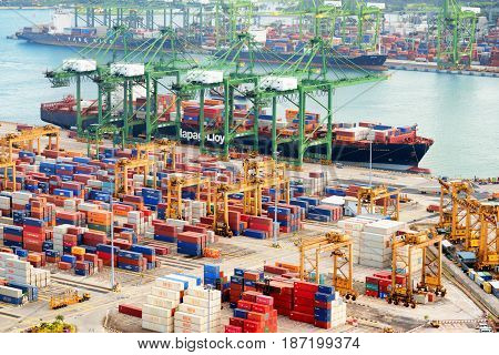 Singapore - February 17 2017: Container terminal at the Port of Singapore. Cargo ship docked in harbor. Ship-to-shore (STS) gantry cranes loading and unloading vessels at shipping yard.