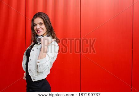 Stylish Woman Standing Near Red Wall