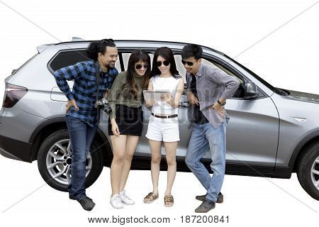 Image of young woman and her friends using a digital tablet while leaning on a car isolated on white background