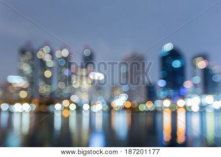 Twilight blurred bokeh city office building light with water reflection abstract background