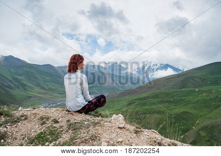 Female with red hairs enjoing stunning landscape of mountains. Dark clouds on the sky.