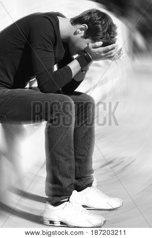 Desperate and frustrated young boy crying. Hands on his face, sitting on a wall. Youth Issues. Outdoors, anxiety and nervousness. Radial blur to amplify the sense of confusion. Black and white.
