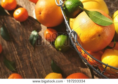 Basket with appetizing fresh citrus fruits on wooden background