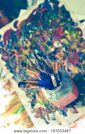 Brushes for drawing stand in a glass with a bristle upwards in a picture from smears with oil paints.