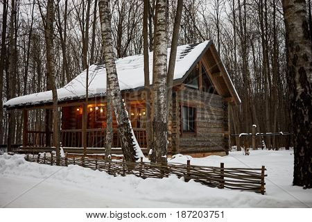 Wooden log-house with illuminated veranda in winter forest.