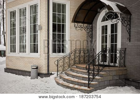 House of bricks, stone steps of porch with metal handrails and entrance canopy in winter.