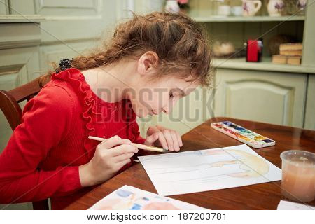 Girl draws watercolors sitting at table in room.