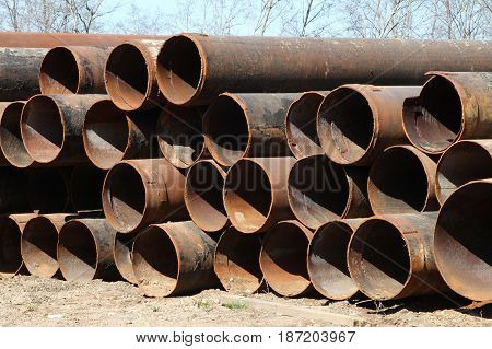 Large diameter pipes stored on the ground.