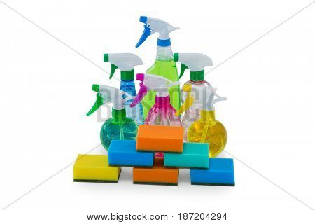 High angle view of stacked sponges with spray bottles against white background