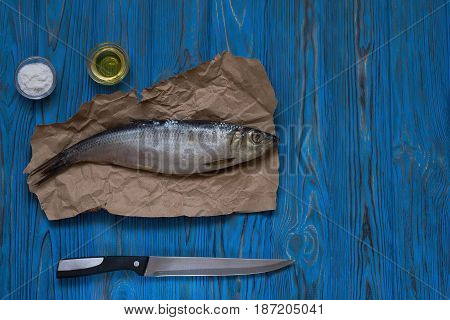 uncooked Herring on paper Salt oil and knife on wooden table. Top view