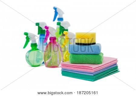 Spray bottles with wipe pads and sponges against white background
