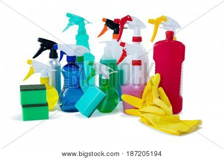 Close up of colorful spray bottles with sponges and gloves against white background