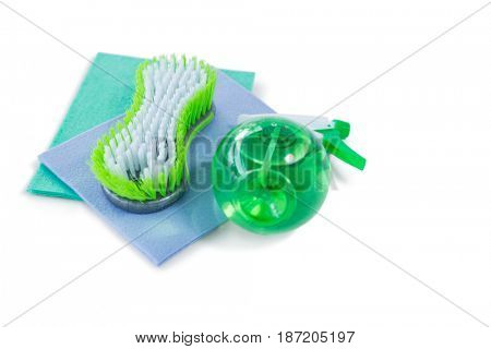 High angle view of brush and spray bottle with wipe pad against white background