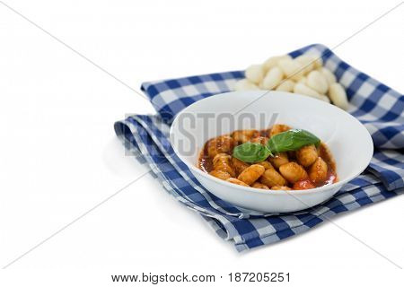 High angle view of gnocchi pasta in bowl on napkin against white background