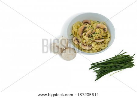 Pasta served in bowl by mushrooms and scallion against white background