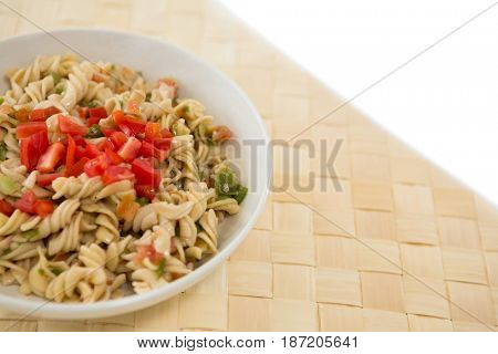Close up of rotini served in bowl on place mat over white background