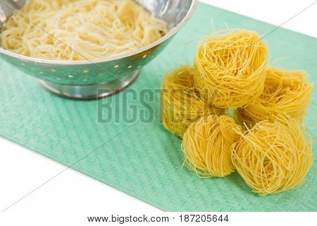 High angle view of pasta in colander with tagliolini on place mat over white background