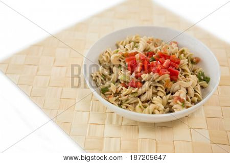 High angle view of rotini served in bowl on place mat against white background