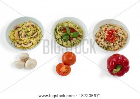 Mushroom with tomato and red bell pepper by various pastas served in bowl against white background