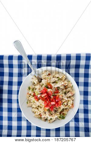 Overhead view of pasta served in bowl on napkin against white background
