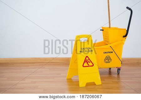 Yellow sigh boad with mop bucket on hardwood floor against wall poster