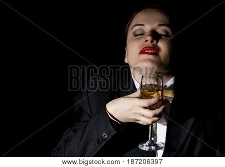 Strange girl in a man's suit drinks champagne, wildly laughs on a dark background
