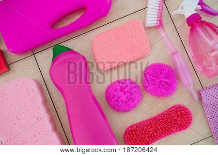 Close up of pink cleaning products on tiled floor