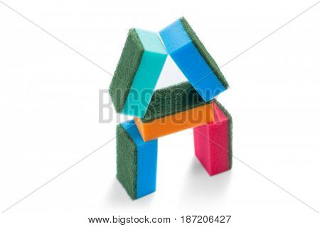 Close up of colorful sponges arranged against white background