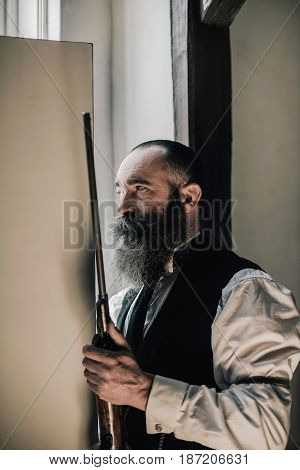 Man With Long Beard Holding Rifle Looking Through Gap Of Light Of Open Door.