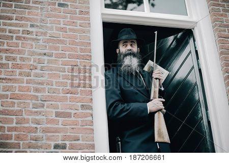 Alert Man With Long Beard Standing With Rifle In Door Post.