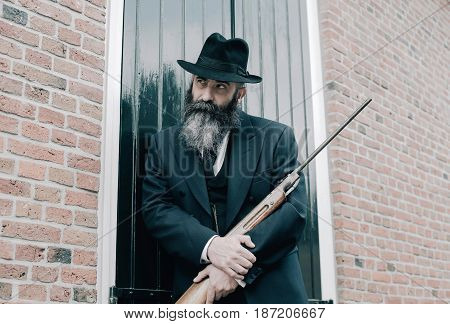 Man With Hat And Long Beard Standing With Rifle Against Window Shutters.