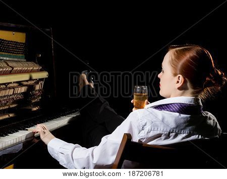 female musician dressed in a man's suit sitting next to the piano and drinks champagne on a dark background