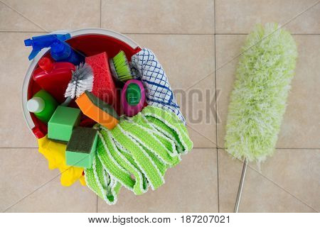 Overhead view of duster by various cleaning products in bucket on tiled floor