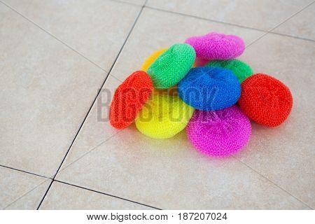 High angle view of colorful sponges on tiled floor