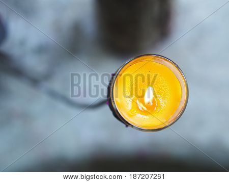 Close up top view of yellow candle in glass on metal stand