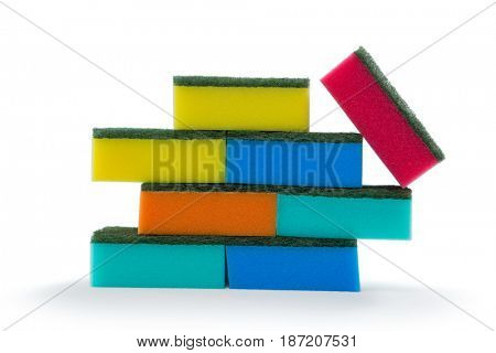 Close up of colorful sponges stacked against white background