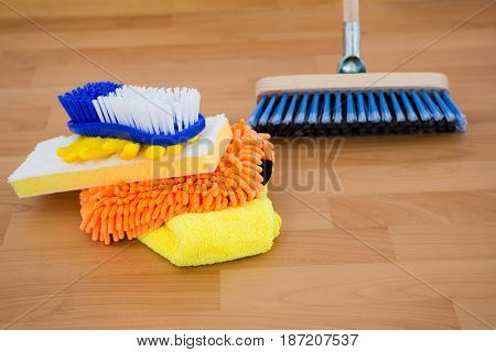 Close-up of sponges and brush by broom on hardwood floor