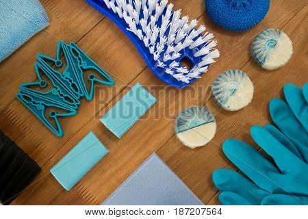 High angle view of cleaning products and brush on wooden table