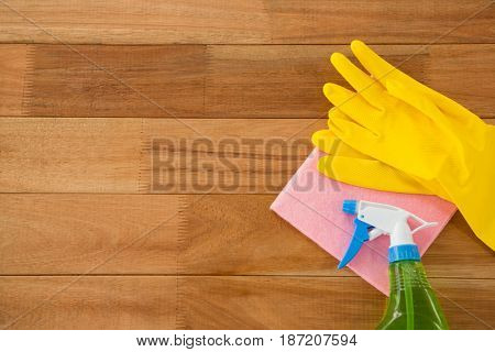 Overhead view of gloves with wipe pad and chemical bottle on wooden table