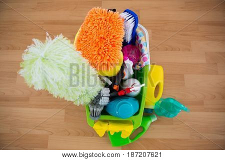 High angle view of duster and cleaning equipment in bucket on hardwood floor