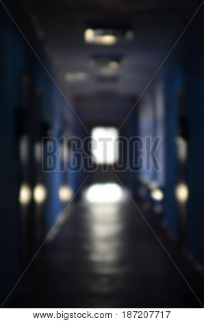 The Blurred Image Of Gloomy Corridor Of A Neglected Public Building. Defocused Picture Of A Public S