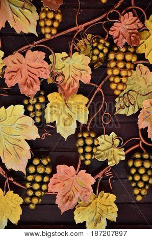 A Photograph Of Forged Grapes, Painted In Warm Orange Tones On A Wooden Background. Background Image