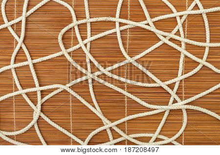 Entangled white rope on a wooden background